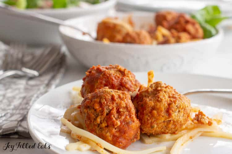 three meatballs on plate with spaghetti in front of platter of meatballs and basil