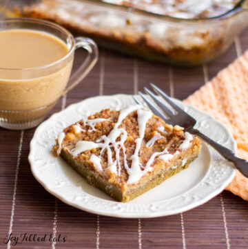 slice of pumpkin dump cake on a white plate with fork next to a glass mug of coffee