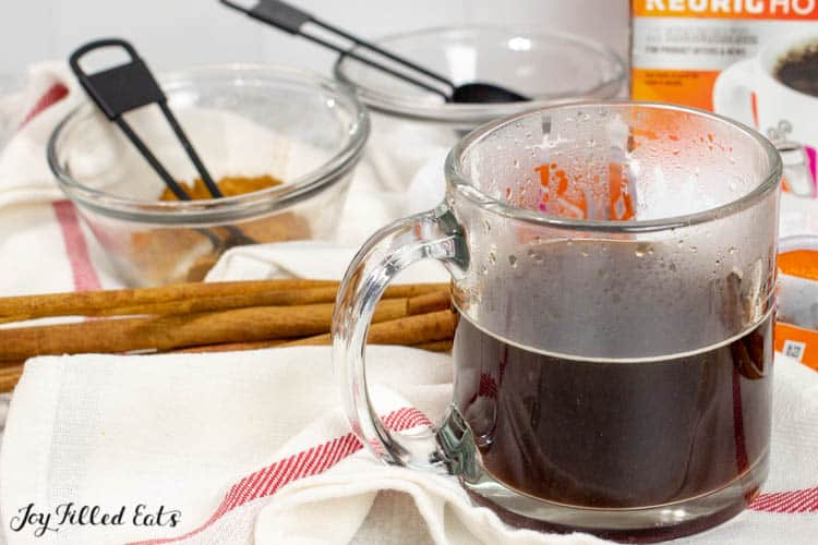 glass mug half filled with coffee surrounded by ingredients to make a snickerdoodle latter, including cinnamon sticks