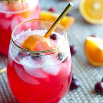 close up on glass and gold straw of vodka cranberry spritzer topped with ice, cranberries and orange peel