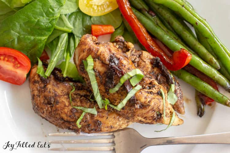 overhead view of white plate with balsamic chicken, spinach and tomato salad and green beans with red peppers