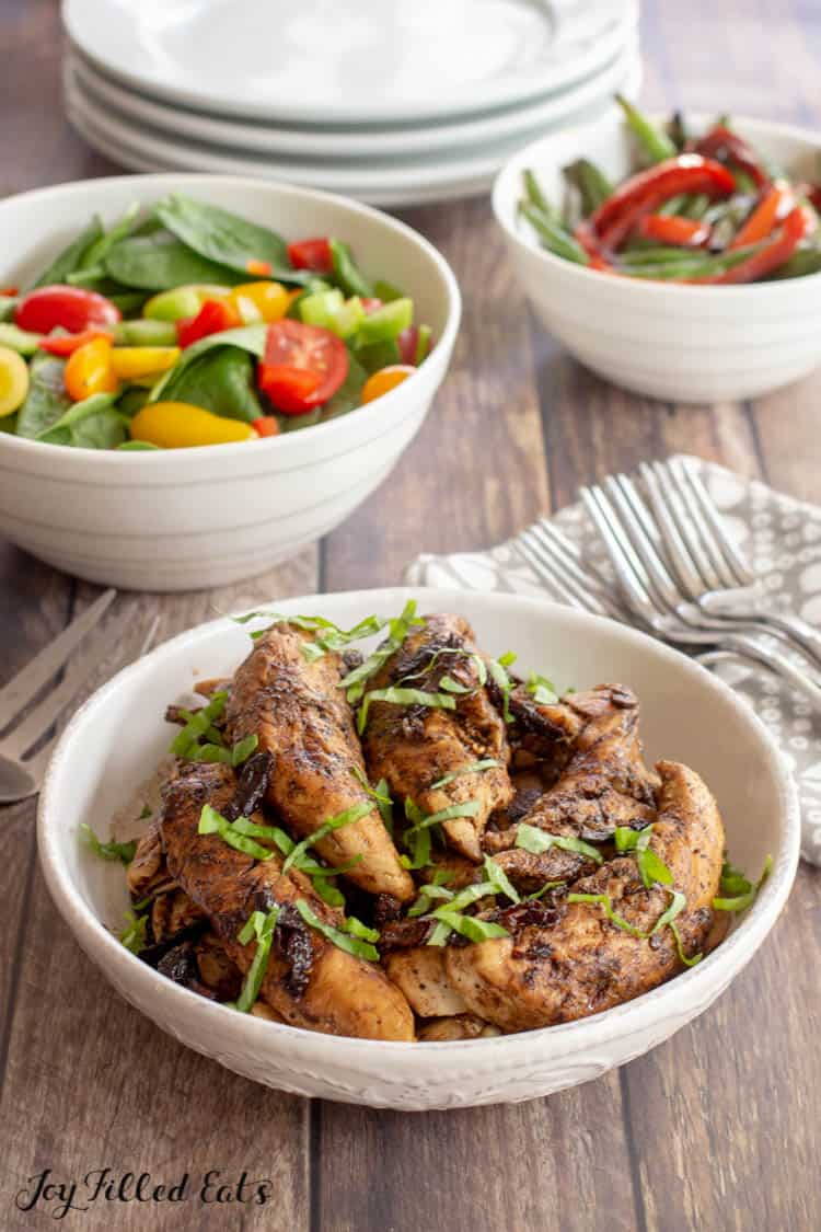 balsamic chicken in a bowl with bowls of green salad and green beans