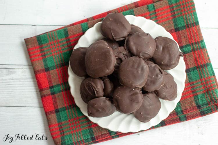 Pile of homemade peppermint patties on white plate on top of decorative plaid napkin