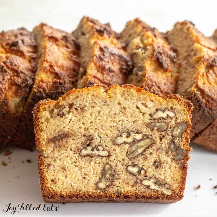 slices of keto banana bread standing upright with one slice leaning on pile exposing nuts within bread