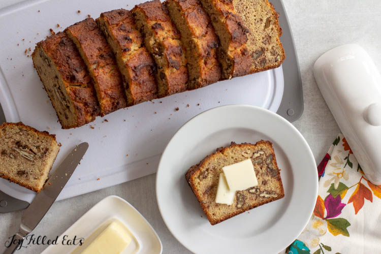 slice of keto banana bread on white plate with two pads of butter. Next to cutting board covered with banana bread slices and butter knife and dish