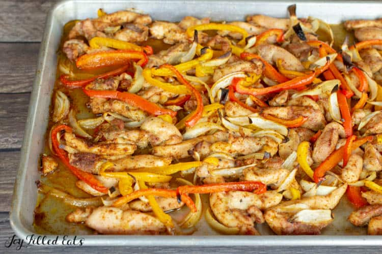 Sheet pan of seasoned chicken, peppers and onions