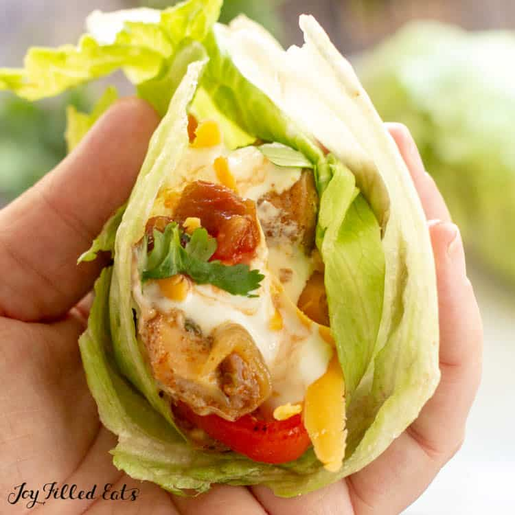 Hand holding lettuce taco of keto chicken fajitas