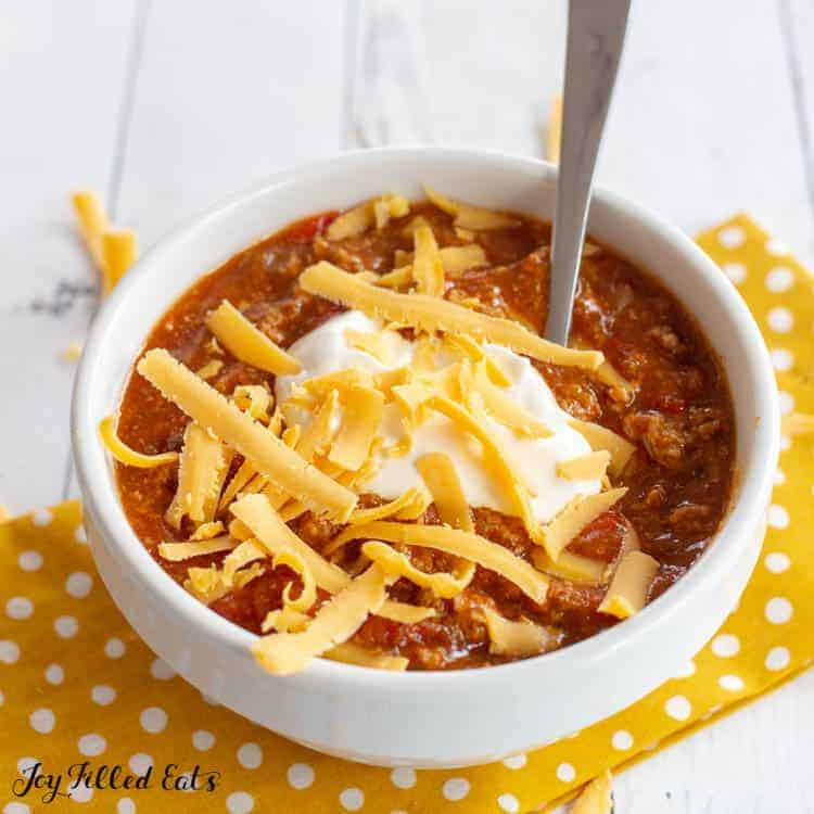 bowl and spoon of instant pot turkey chili topped with sour cream and shredded cheese