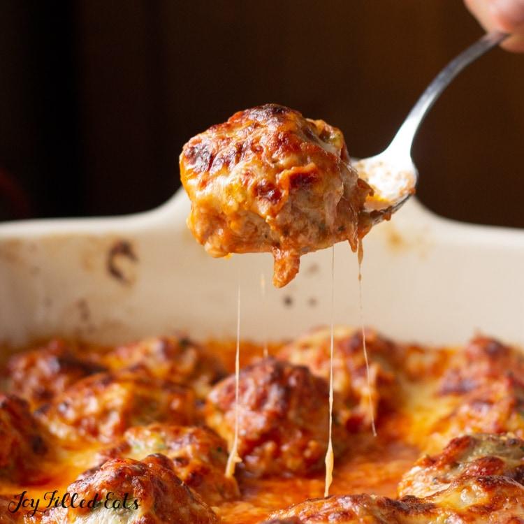 Spoon of cheesy Meatball from Meatball casserole dish below