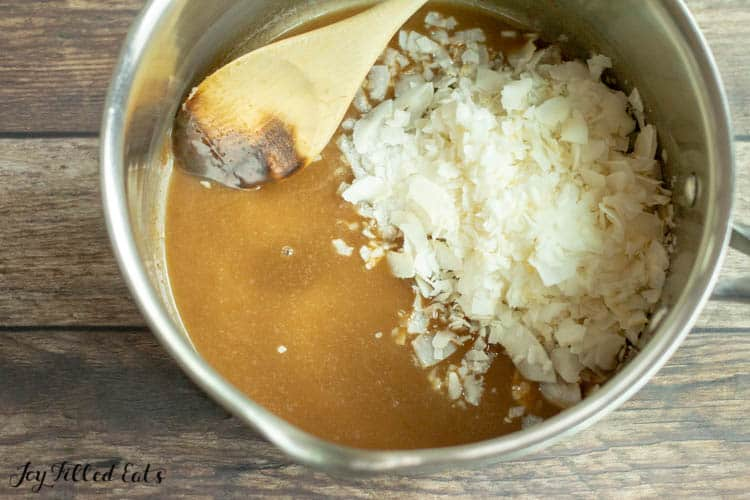 Sauce pan of samoa cookie topping with coconut flakes and wooden spoon