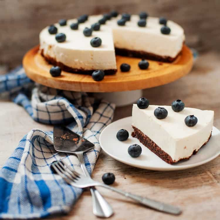 Keto White Chocolate Cake on cake platter with slice cut out. Slice of cake on plate. Both slice and cake topped with blueberries
