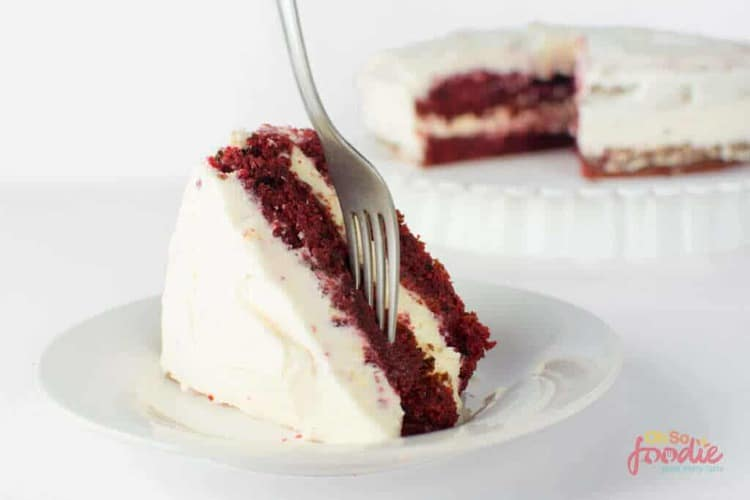 Double layer red velvet cake with fork sticking into slice