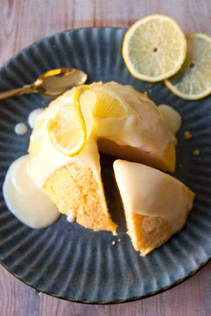 overhead view of lemon mug cake with slice cut out and moved away from main cake. Plate is blue with spoon and circular lemon slices