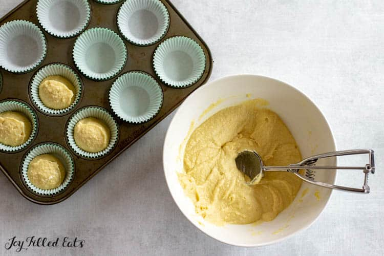 Mixing bowl of almond flour cupcake batter with scoop next to a cupcake tin with half filled cupcake wrappers in mold