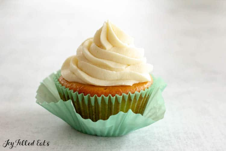 Almond Flour Cupcake topped with buttercream frosting in a light blue cupcake wrapper pulled away from the cupcake.