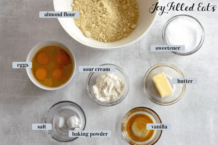 Overhead shot of ingredients for almond flour cupcakes in various bowl containers including almond flour, sweetener, butter, sour cream, eggs, salt, baking powder and vanilla