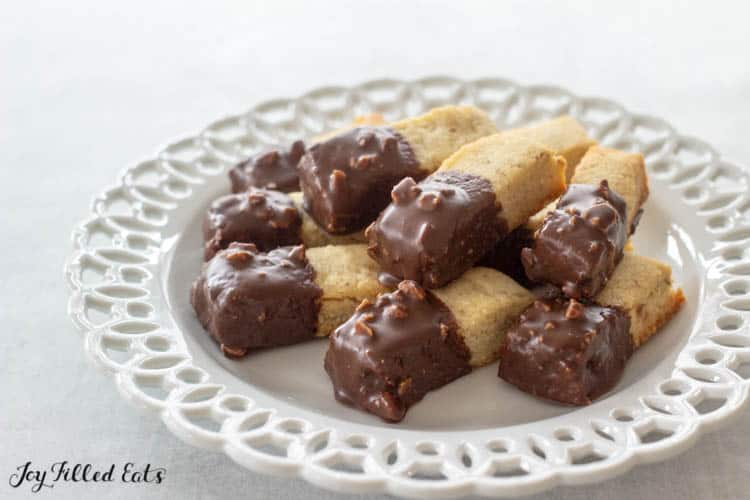 Keto almond shortbread cookies dipped in chocolate on white plate
