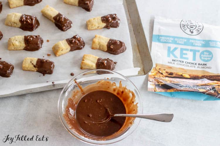 Keto Almond shortbread cookies dipped in chocolate on parchment lined cookie sheet. Next to bowl of melted keto chocolate bark with spoon and keto milk chocolate almond bark packaging.