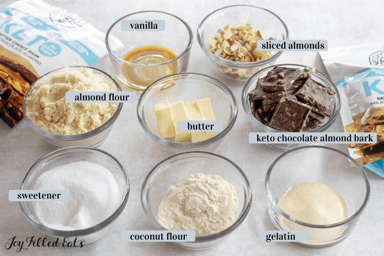 Ingredients for Keto Almond Shortbread cookies in various bowl containers including almond flour, butter, vanilla, sliced almonds, keto chocolate almond bark, gelatin, coconut flour and sweetener