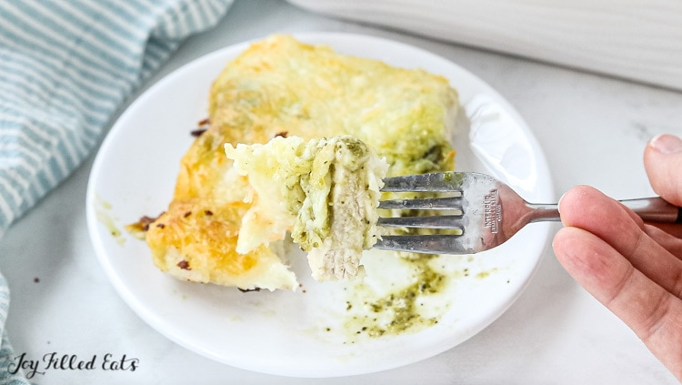 forkful of baked pesto chicken on a white plate