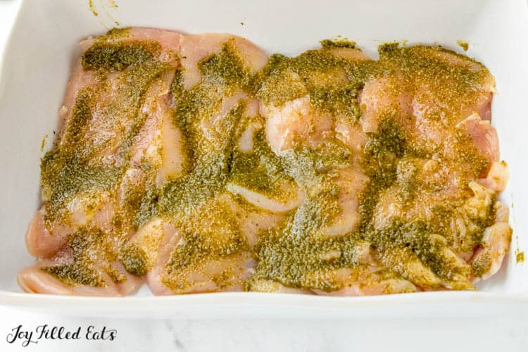 white casserole dish of raw chicken tenders smeared with pesto sauce