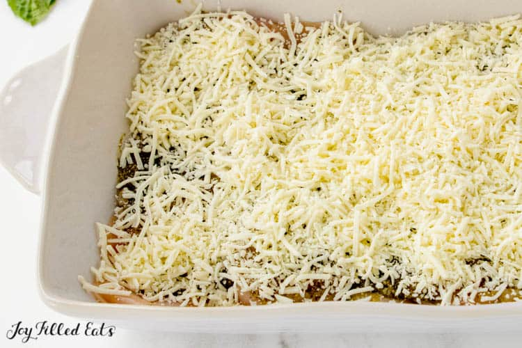 overhead view of white casserole dish with baked pesto chicken before baking, covered in shredded mozzarella cheese