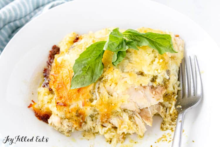baked pesto chicken on a white plate with a fork