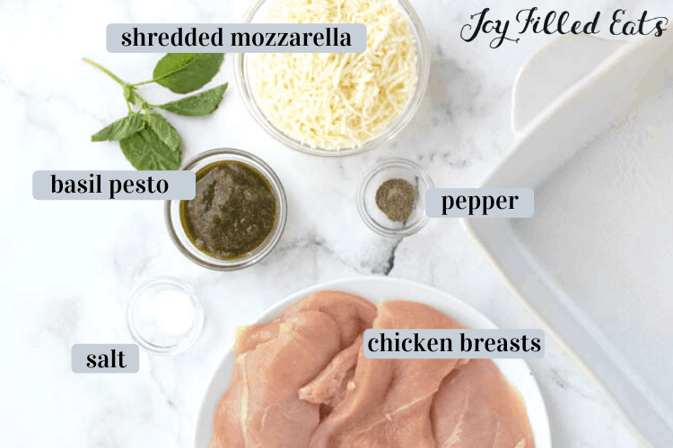 Baked Pesto Chicken ingredients including Chicken tenders, basil pesto, salt, pepper and shredded mozzarella, all next to a white casserole dish