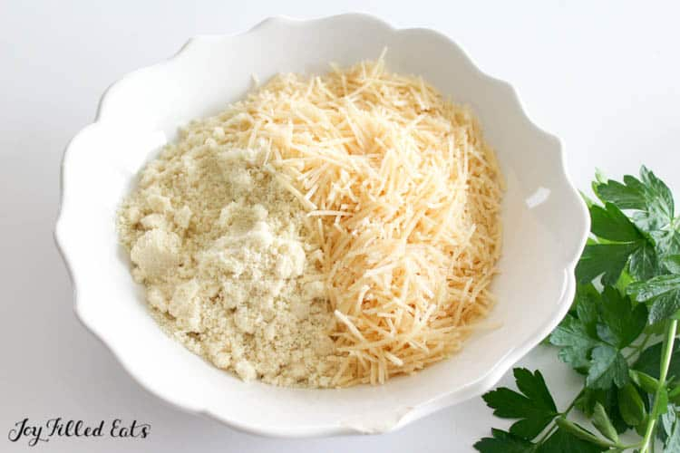 Small dish of shredded cheese and almond flour next to bundle of parsley