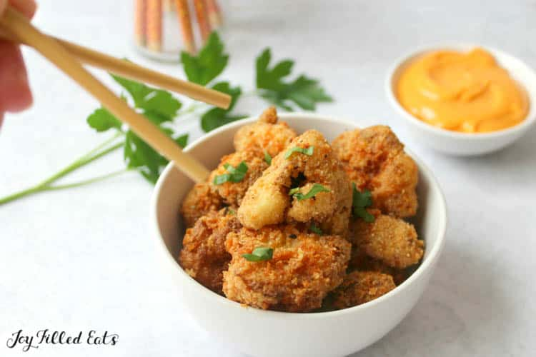hands with chopsticks reaching for keto fried cauliflower