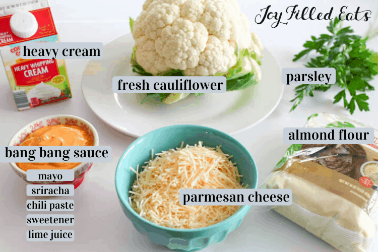 Keto Bang Bang Cauliflower ingredients including heavy cream, a head of cauliflower, parsley, almond flour, Parmesan cheese, and bang bang sauce