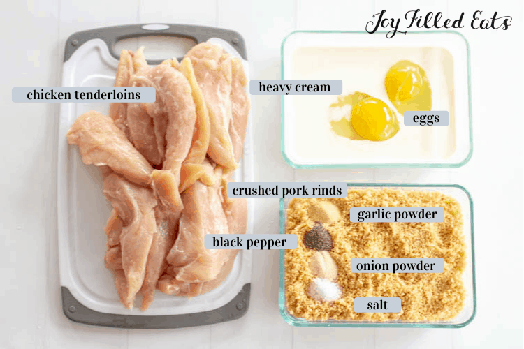 Healthy Baked Chicken Tender ingredients. Raw Chicken tenders on cutting board, next to wet ingredients in bowl of heavy cream and eggs, next to bowl of dry ingredients of crushed pork rinds, garlic powder, black pepper, onion powder, salt
