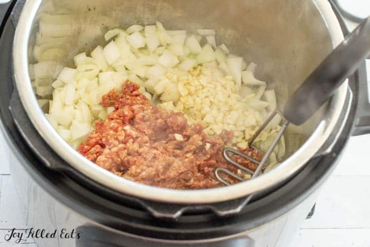 Overhead view of pot filled with ingredients and ground sausage with meat masher