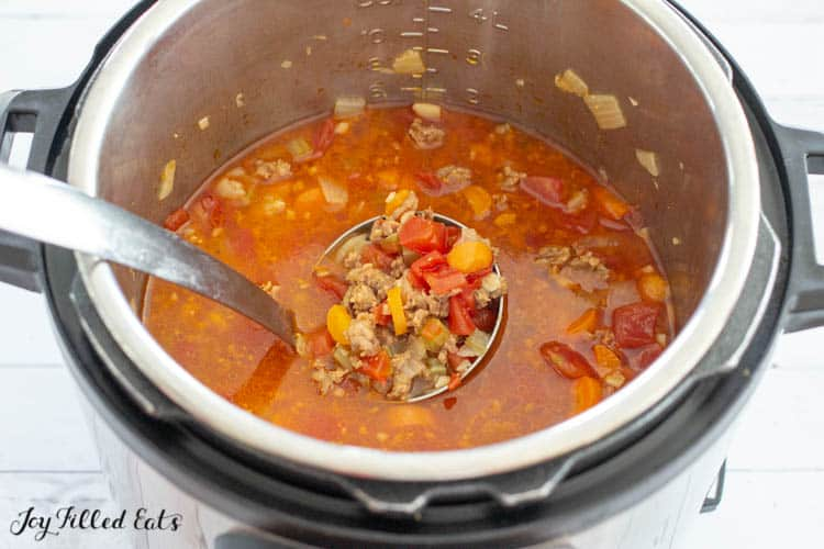 soup with ladle in pot filled with vegetables and meat