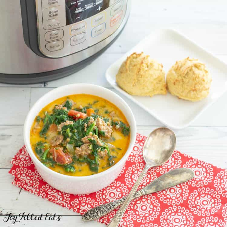 White Bowl of Instant Pot Zuppa Toscana next to square white plate of two biscuits and instant pot. Bowl is on decorative red napkin with spoon and butter knife