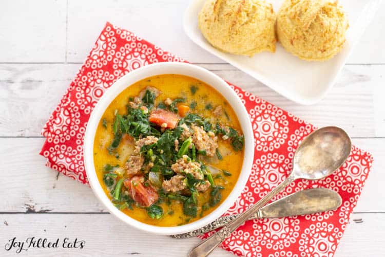 Overhead view White Bowl of Instant Pot Zuppa Toscana next to square white plate of two biscuits. Bowl is on decorative red napkin with spoon and butter knife