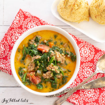 Close up overhead view of White Bowl of Instant Pot Zuppa Toscana next to square white plate of two biscuits. Bowl is on decorative red napkin with spoon and butter knife