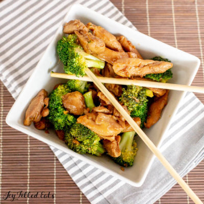 Keto Teriyaki Chicken with broccoli and chop sticks in square bowl on gray and white striped napkin