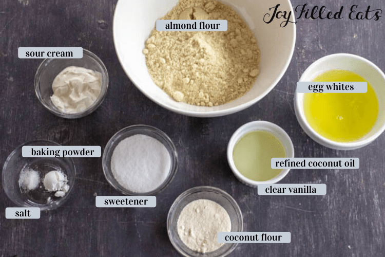Keto Vanilla Cake ingredients in various bowls include almond flour, egg whites, sour cream, baking powder, salt, sweetener, coconit flour, clear vanilla and refined coconut oil