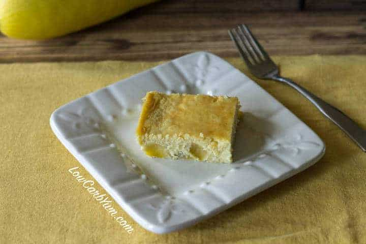 Yellow squash custard cake on square white plate with fork