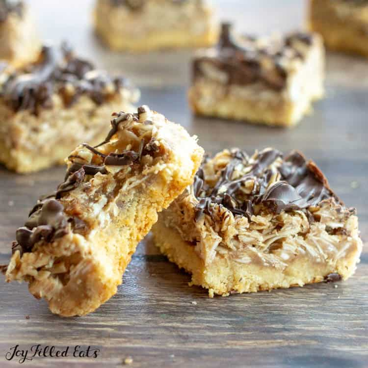 Close up on two Samoas Cookie Bars with bite taken out of one. Scattered Samoas cookie bars in background.