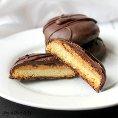 Tagalong cookies on plate with one cookie cut in half to see inside layers