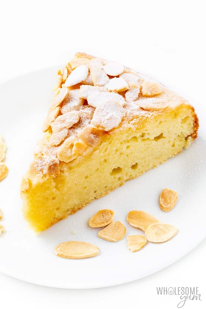 Slice of yellow almond cake on white plate with scattered sliced almond around