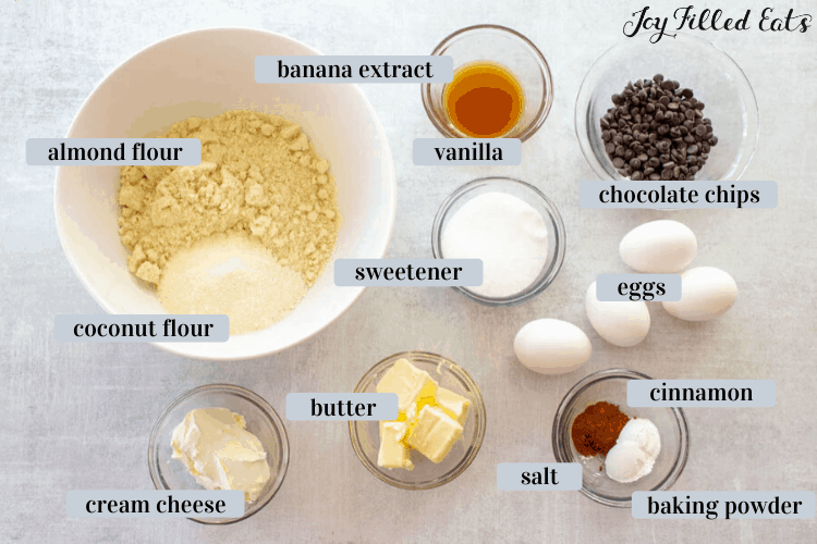 ingredients for almond flour banana muffins including white bowl of almond flour and coconut flour, small mixing dish of banana extract and vanilla, chocolate chips, sweetener, 4 eggs, butter, cream cheese, salt, baking powder and cinnamon