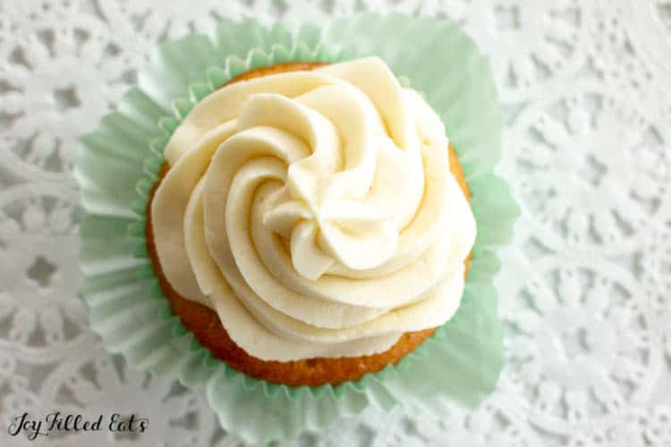 Overhead shot of Almond Flour Cupcake topped with buttercream frosting in a light blue cupcake wrapper pulled away from the cupcake. Sitting on a decorative table cloth