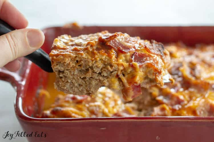 Serving Spatula holding piece of bbq meatloaf with red casserole dish in background