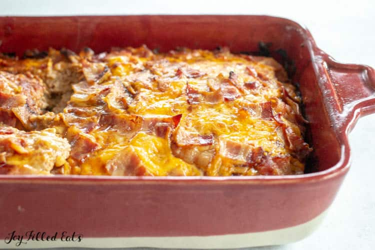 Red Casserole dish filled with bbq meatloaf topped with melted cheese and bacon