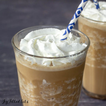 Close up of two Skinny Frappuccino topped with whipped cream with blue and white patterned paper straw
