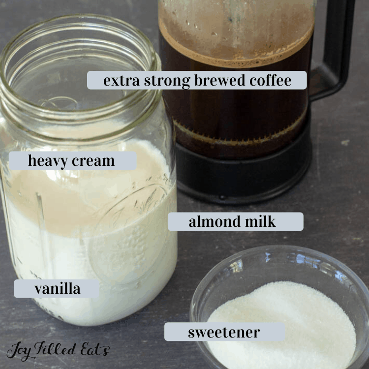 skinny frappuccino and latter base ingredients of extra strong brewed coffee, a mason jar of almond milk, heavy cream and vainilla, and a small dish of sweetener