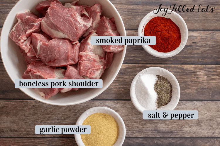 Keto pulled pork ingredients include a bowl of boneless pork shoulder, smoked paprika, salt and pepper, and garlic powder